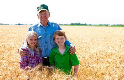 An older farmer standing with his arms around two young children in a wheat field.