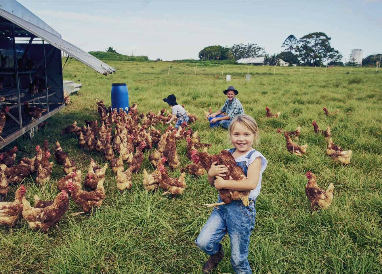 A young girl holding a chicken in a field, while a farmer and another child look on in the background.